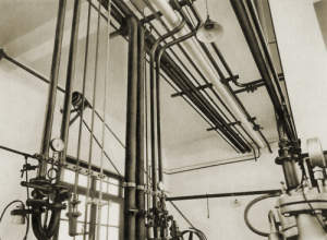 "Photograph of ""An intricate network of pipes: water, stema, coolant, different classes of vacuum, and pressurized gases,..."""